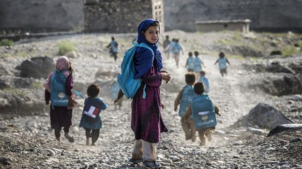 Afghan children run to school on Sept. 24. Whoever takes over as the next U.S. president will have to determine how many troops will remain after the December 2014 deadline to help with long-term security. (AFP/Getty Images)