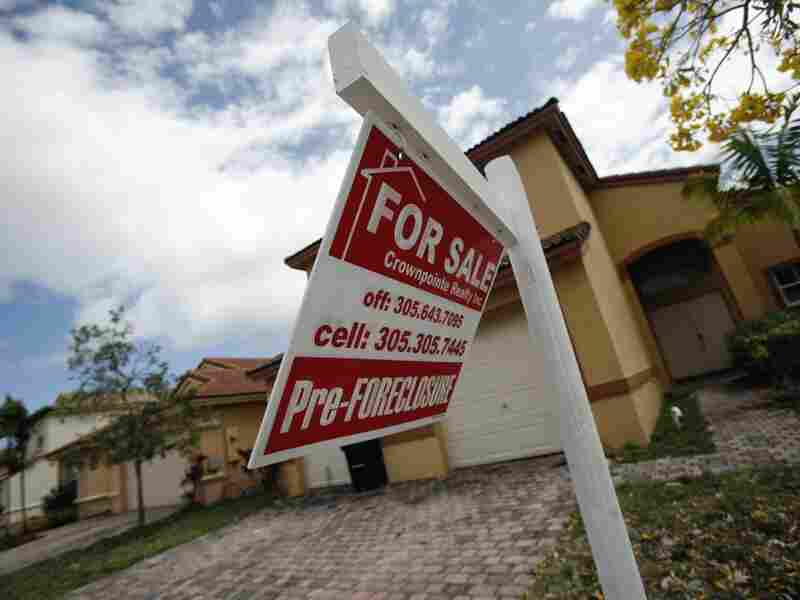 A for-sale sign hangs in front of a Homestead, Fla., home. In terms of the housing market, the presidential candidates differ most on regulation.