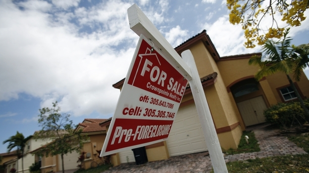 A for-sale sign hangs in front of a Homestead, Fla., home. In terms of the housing market, the presidential candidates differ most on regulation. (AP)