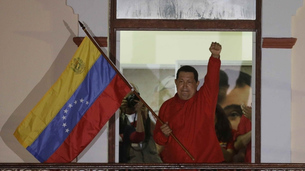 President Hugo Chavez waves a Venezuelan flag as he greets supporters at the Miraflores presidential palace balcony in Caracas on Sunday. Chavez won re-election and a new endorsement of his socialist project Sunday, surviving his closest race yet after a bitter campaign against opposition candidate Henrique Capriles. (AP)