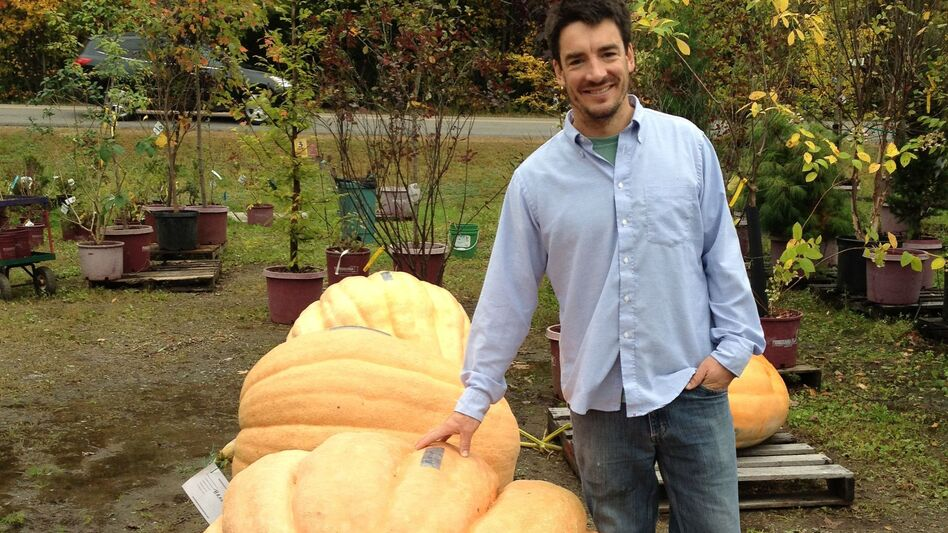 Topher Mallory stands next to the pumpkin he turned into a first-place-winning powerboat. (Maine Public Radio)