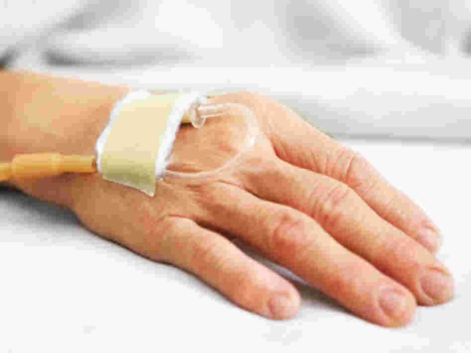 A woman's hand with an IV in a hospital bed.
