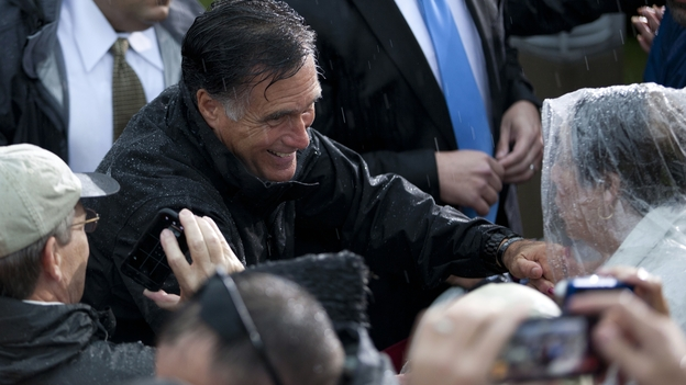 Republican presidential candidate Mitt Romney shakes hands during a rainy campaign rally Monday in Newport News, Va. (AP)