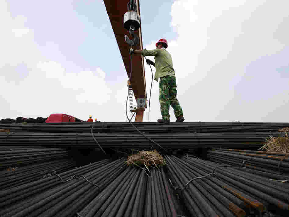 In China's Anhui province, a worker unloads steel bars at a factory. A slowdown in China and other major nations threatens to pull the global economy into recession, the International Monetary Fund warns.