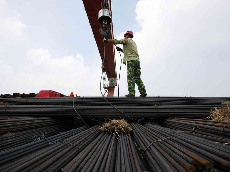 In China's Anhui province, a worker unloads steel bars at a factory. A slowdown in China and ot