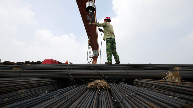 In China's Anhui province, a worker unloads steel bars at a factory. A slowdown in China and other major nations threatens to pull the global economy into recession, the International Monetary Fund warns. (AFP/Getty Images)
