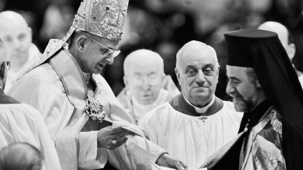 Pope Paul VI hands Orthodox Metropolitan Meliton of Heliopolis a decree during the December 1965 session of the Roman Catholic Ecumenical Council in Vatican City. The decree cancels excommunications that led