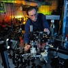 """NIST physicist and Nobel Prize-winner David Wineland adjusts an ultraviolet laser beam used to manipulate ions in a high-vacuum apparatus containing an """"ion trap."""" These devices have been used to demonstrate the basic operations required for a quantum computer."""