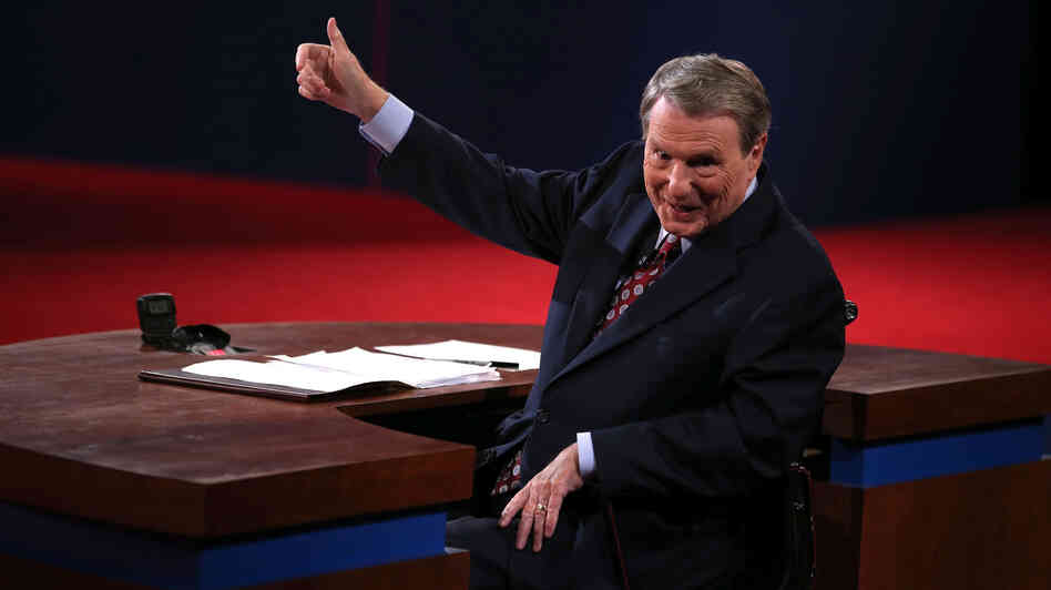 Moderator Jim Lehrer gestures before the presidential debate at the University of Denver last week. Moderators must finagle answers out of sometimes-dodgy politicians and keep control, all without seeming to get in the