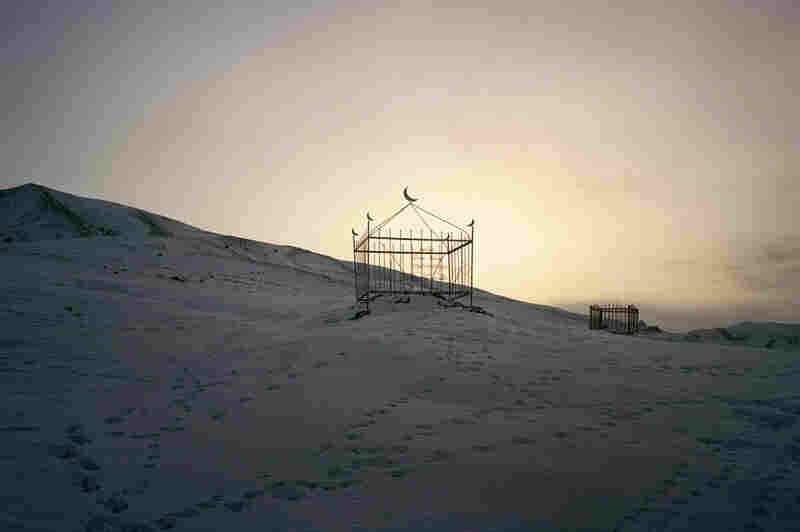 A Kyrgyz grave is seen on a hillside slope near the Kuruman family's village. The Kuruman parents, retired from the nomadic life, stay in a village of mud-and-thatch houses with a small herd of livestock.