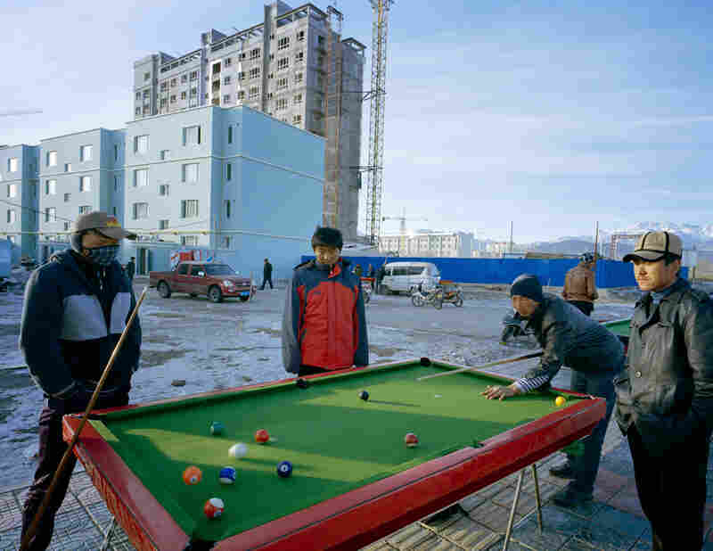 New residents of an apartment building in Wuqiaxian play pool outside. Some youth see a new highway as an opportunity, Takayama says. It will generate inward and outward fluidity of people, goods and culture.