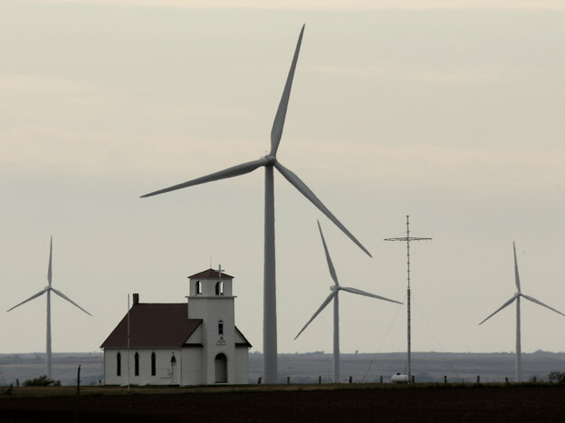 Wind turbines dwarf a church near Wilson, Kan. The Whit