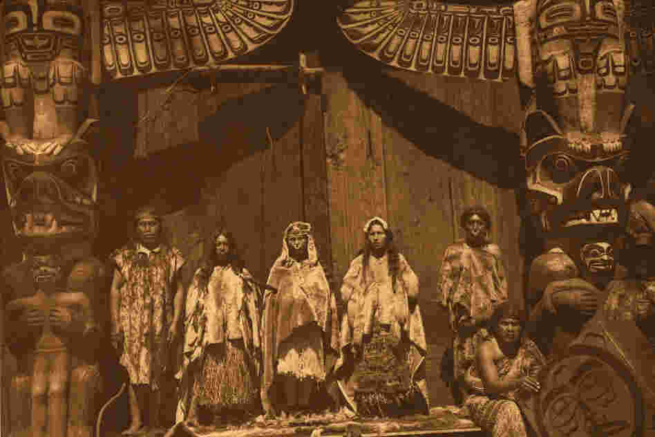 "The original caption reads: ""The [Kwakiutl] bride stands in the middle between two dancers hired for the occasion. Her father is at the left, and the bridegroom's father at the right behind a man who presides over the box-drum."""