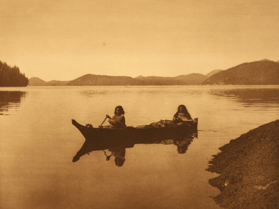 """Two Hesquiat women,"" reads the Curtis caption, ""are homeward bound with the product of their day's labor in gathering food, and cedar-bark to be used in making mats."""