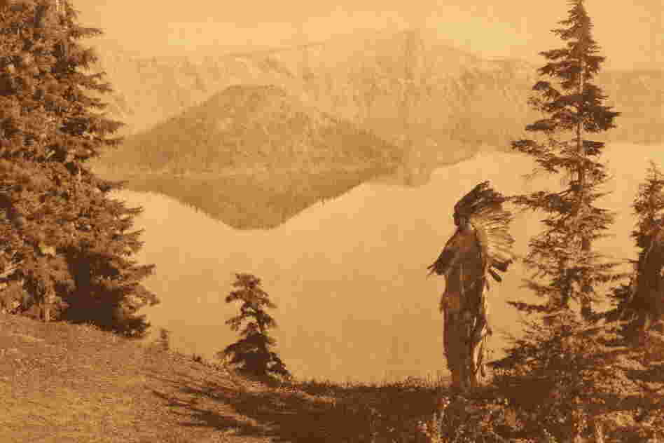 "For a photo simply titled ""Chief — Klamath,"" the caption reads: ""The subject of this plate, in deerskin suit and feathered war-bonnet of the Plains culture, is shown against a background of Crater lake and its precipitous rim towering a thousand feet above the water."""