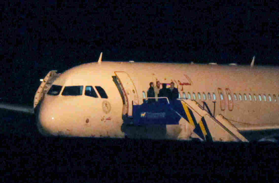 People speak atop the aircraft steps of a Syrian passenger plane that was forced by Turkish jets to land at Esenboga airport in Ankara, Turkey, early Thursday.