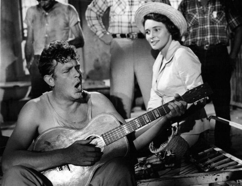 Andy Griffith playing guitar as Patricia Neal watches in a scene from the Elia Kazan's <em>A Face In The Crowd</em>.