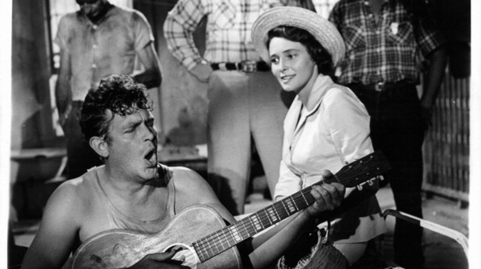 Andy Griffith playing guitar as Patricia Neal watches in a scene from the Elia Kazan's A Face In The Crowd. (Getty Images)