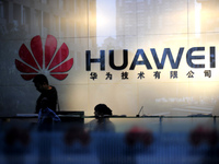 """Staff and visitors walk past the lobby at the Huawei office in Wuhan, China. Beijing has urged Washington to """"set aside prejudices"""" after a draft congressional report said Chinese telecom firms Huawei and ZTE were security threats that should be banned from business in the U.S."""