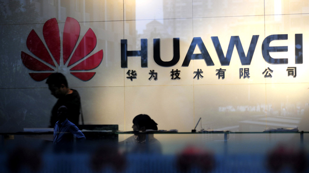 "Staff and visitors walk past the lobby at the Huawei office in Wuhan, China. Beijing has urged Washington to ""set aside prejudices"" after a draft congressional report said Chinese telecom firms Huawei and ZTE were security threats that should be banned from business in the U.S. (AFP/Getty Images)"