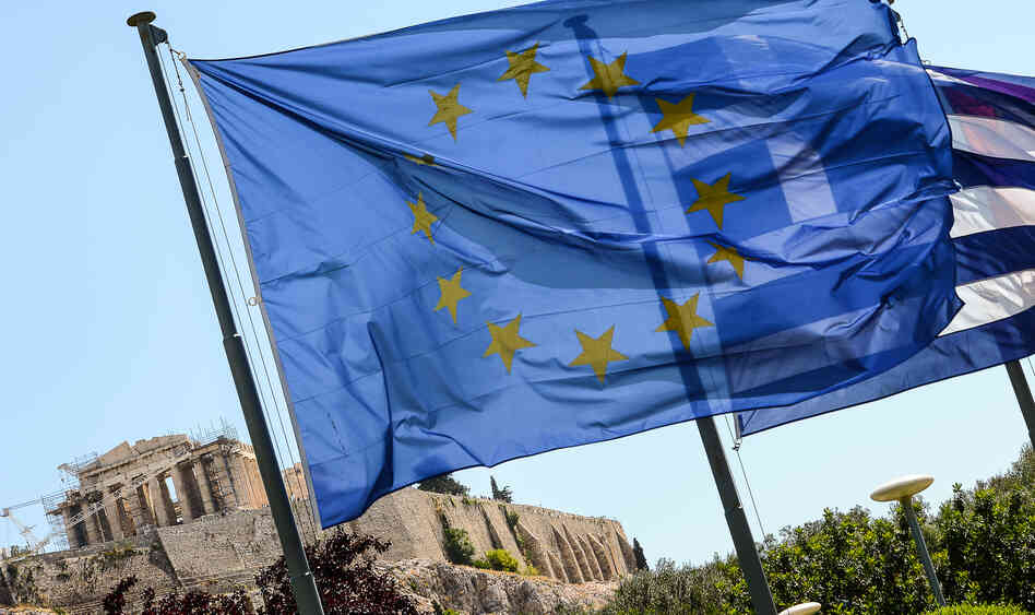European Union flag and Greek flag wave in front of the Acropolis, in central Athens.
