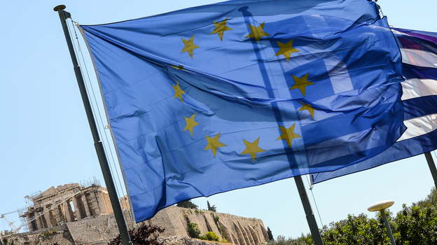 European Union flag and Greek flag wave in front of the Acropolis, in central Athens. (AFP/Getty Images)