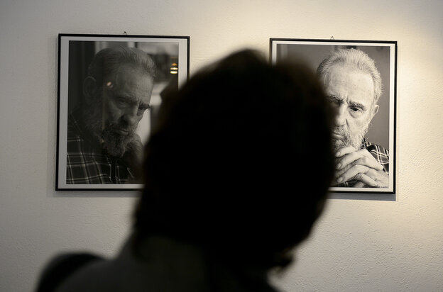 A visitor watches pictures taken by Cuban photographer and cinematographist Alex Castro, son of former Cuban president Fidel Castro.