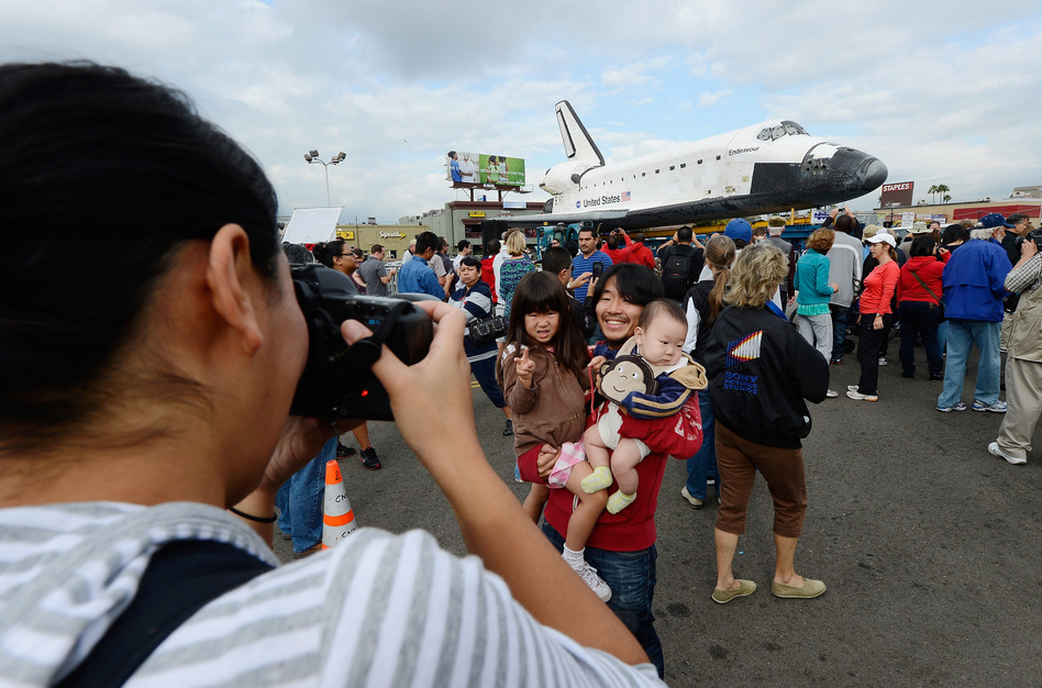 Mifumi Nakajima takes a picture of her husband Nozomo Nakajima holding their children Leigha Nakajima, 3, and Eli Nakajima, 6 months, in front of the space shuttle Endeavour parked in a mall parking lot. (Getty Images)