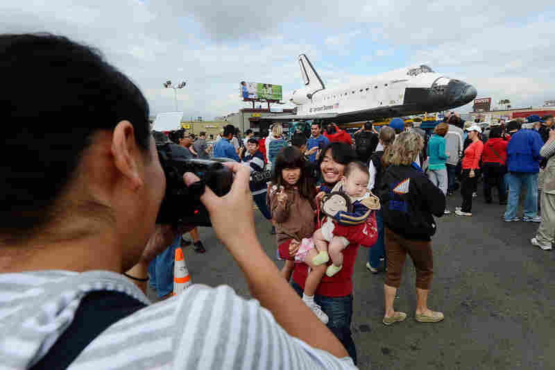 Mifumi Nakajima takes a picture of her husband Nozomo Nakajima holding their children Leigha Nakajima, 3, and Eli Nakajima, 6 months, in front of the space shuttle Endeavour parked in a mall parking lot.