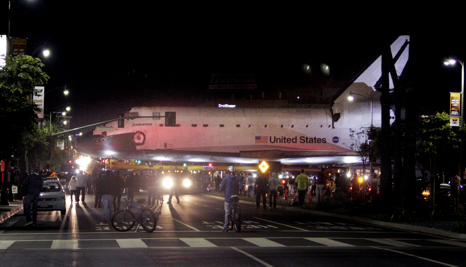 The space shuttle Endeavour leaves Los Angeles International Airport hangar for the streets of Los Angeles in the early morning. (AP)