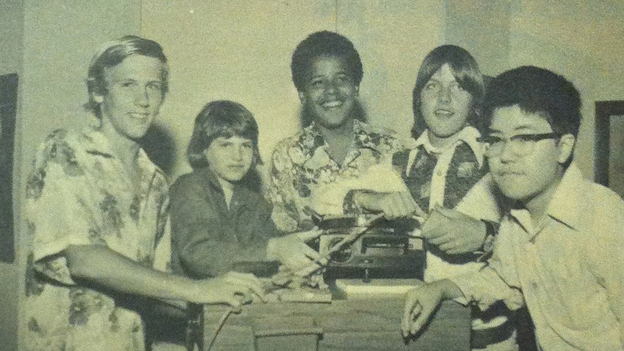 """Barack Obama in a 1975 photo from the Punahou School yearbook. He and his eighth-grade homeroom classmates pose with a slide projector as part of the yearbook's theme of """"Nostalgia."""" (Punahau School 1974-1975 Yearbook)"""