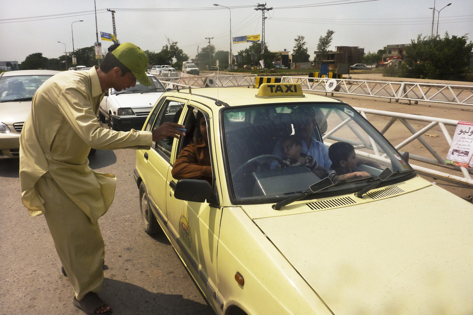 Khan Wali, 21, scrutinizes passing cars for young children at the traffic checkpoint. If a child appears to be younger than 5, the driver must pull over. (NPR)