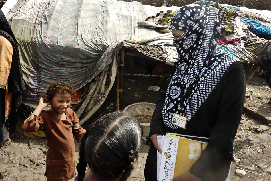 Social mobilizers like Awaiz Amjad (right) walk through dense slums and go door to door inoculating children. Many children are malnourished, with weak immune systems. (NPR)