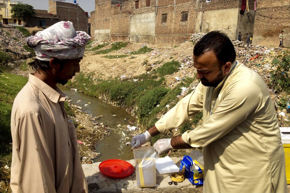 Health care workers take samples of sewage water to check for the polio virus in Rawalpindi, a city near Islamabad known to be at high-risk for polio. (NPR)