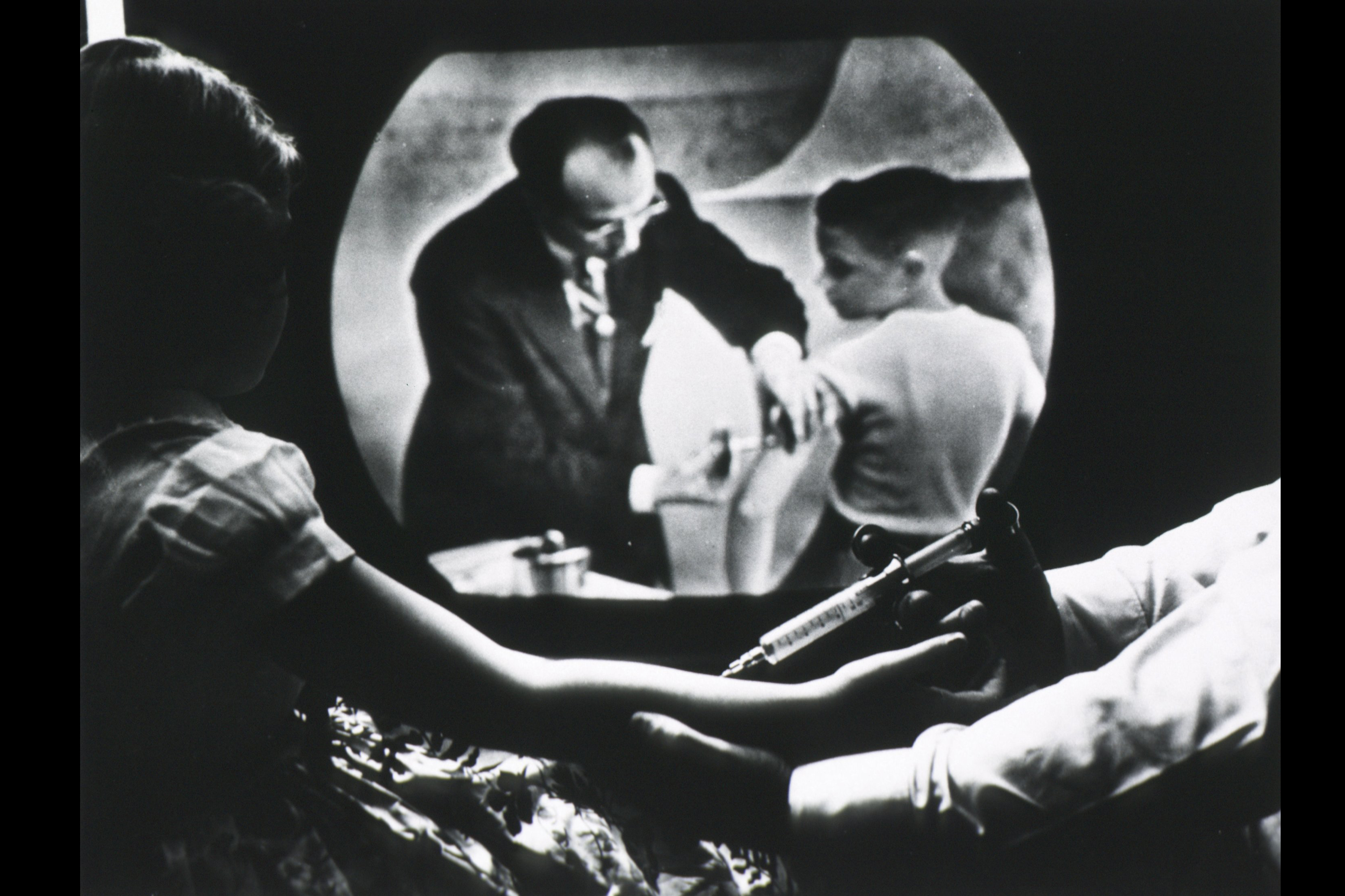 While receiving a polio vaccine, Cheryl Halpin watches Salk inoculate another child on television.