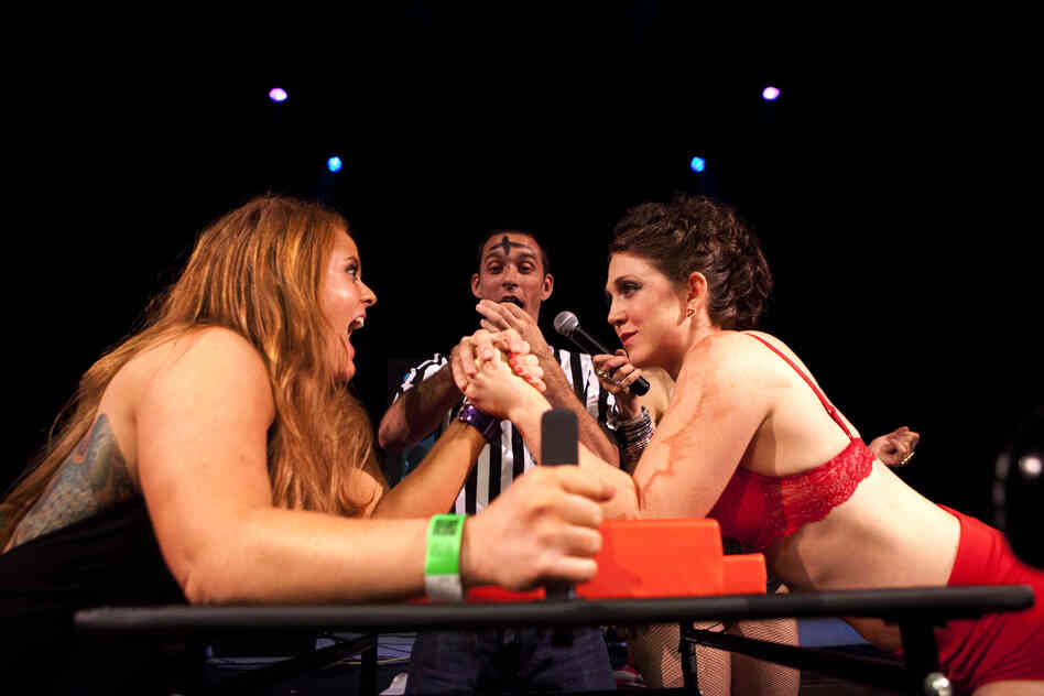 """Ze Dirty Butcher,"" (right) locks elbows with ""Pain Fonda"" in her first match of the night. Dyer lost the bout, but got her pride back in a dance-off rematch."
