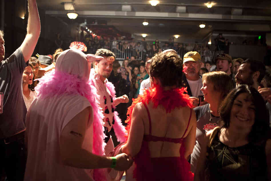 Dyer is greeted by her entourage of burlesque pigs after losing her match. Her husband Cliff, seen here with a pig nose on his forehead, was there to greet her.