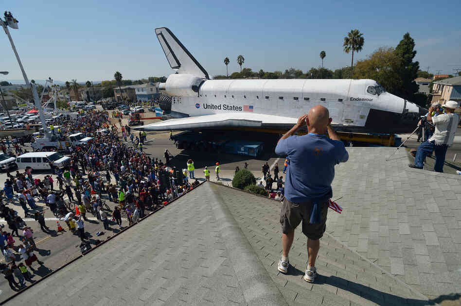 At every turn of Endeavour's stop-and-go commute through urban streets, a constellation of spectators trailed along as the space shuttle ploddingly nosed past stores, schools, churches and front yards.