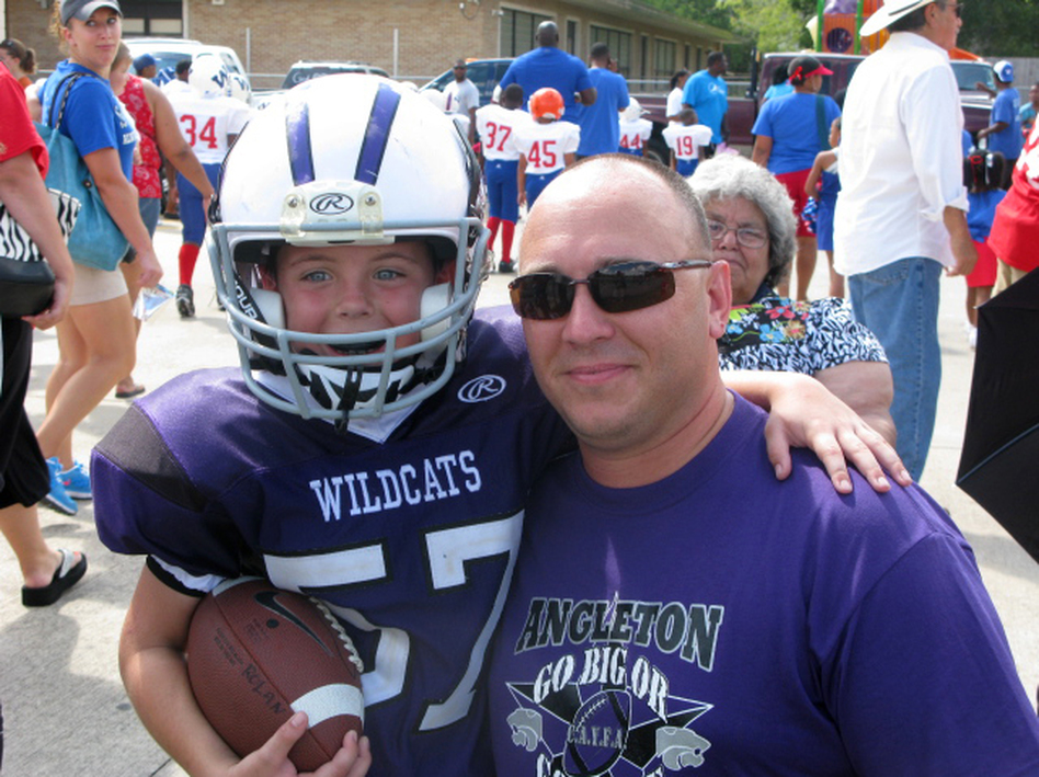Bryce Rolan, 8, and his dad, Wesley, at a Wildcat game in Angleton, Texas. At 4 feet 2 inches and 65 pounds, Bryce is playing his first year of tackle football. (NPR)