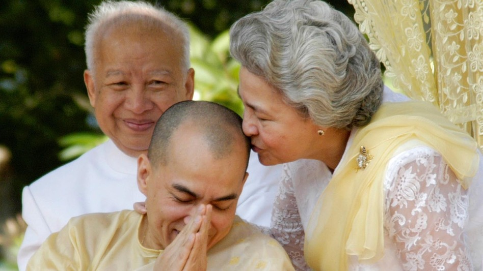 Sihanouk looks on as his wife, Queen Monineath, kisses his son and successor, King Norodom Sihamoni, at a coronation ceremony at the Royal Palace in Phnom Penh on Oct. 29, 2004.