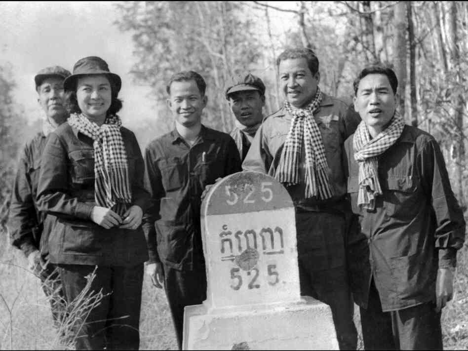 Sihanouk (second from right) poses with Khieu Samphan (third from left), a top Khmer Rouge leader, next to a milestone marking the distance to Phnom Penh, the Cambodian capital, in 1973.