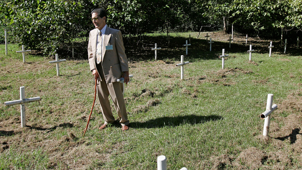 Dick Colon, one of the White House Boys, walks through grave sites near the Dozier School for Boys in Marianna, Fla. Several men who suffered abuse and severe beatings believe the crosses mark the graves of boys who were killed at the school, victims of punishments that went too far. (AP)
