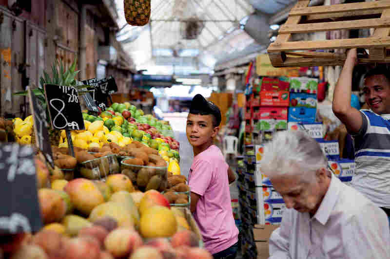 A boy chooses fruit from a stall as Jerusalem market vendors swirl around him.