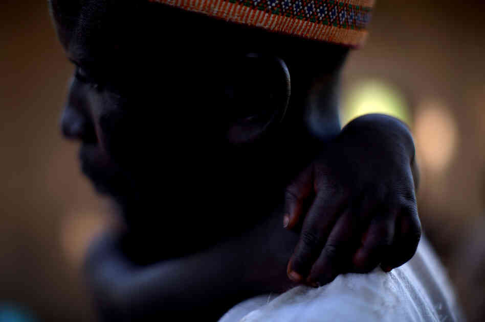 Adamu Ali carries his 4-year-old son, Omar, who was stricken with polio earlier this year. They live in the village of Minjibir.