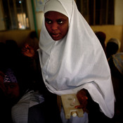 Sahya Idriss, a service provider at the health clinic in Minjibir, carries a vial of the polio vaccine.