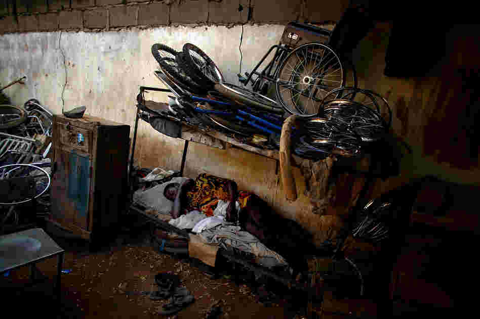 A man naps at a scooter and tricycle shop run by polio victims in Kano.