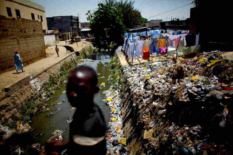 A child crosses a bridge over the cement-lined Gogo stream, which flows behind the main market in Kano. Sanitation workers regularly test the sewage here for the presence of the polio virus.