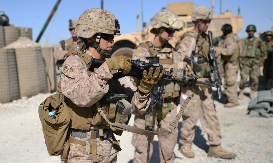 Female Marines unload their rifles after a patrol with Afghan soldiers in Helmand province in June. The Marine Corps leadership has started an experiment to determine whether female Marine lieutenants have what it takes to become infantry officers and lead on the battlefield.