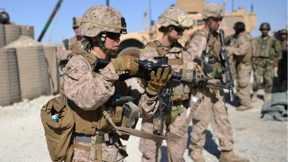 Female Marines unload their rifles after a patrol with Afghan soldiers in Helmand province in June. The Marine Corps leadership has started an experiment to determine whether female Marine lieutenants have what it takes to become infantry officers and lead on the battlefield. (AFP/Getty Images)