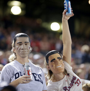 Fans wear President Obama and Mitt Romney masks at the Atlanta Braves-Miami Marlins game Sept. 25 in Atlanta. One of many quirky election year predictors is based on which candidate's likeness sells better as a Halloween mask.